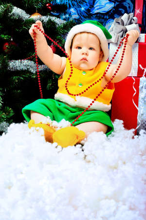 Beautiful child sitting with presents against Christmas background. photo