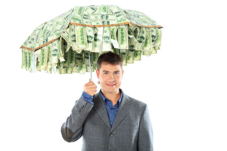 profiting: Business concept: businessman holding an umbrella of money. Isolated over white.