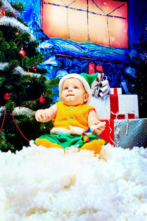 Beautiful child sitting with presents against Christmas background. Stock Photo - 11261606