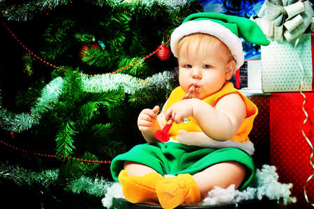 christmas costume: Beautiful child sitting with presents against Christmas background. Stock Photo