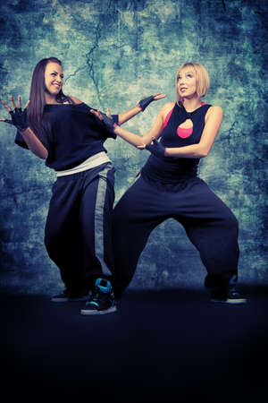 Modern teenage girls dancing hip-hop at studio. photo
