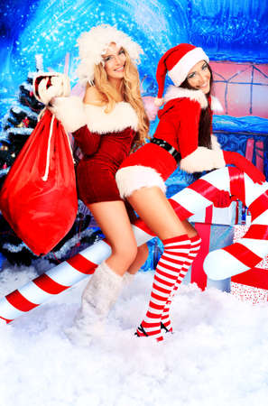 Two sexy young women in Christmas clothes posing over Christmas background.