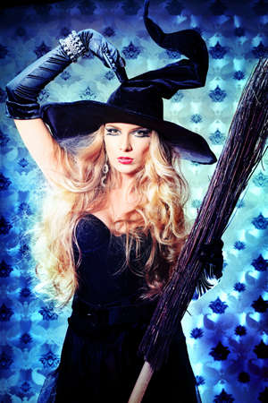 Charming halloween witch with broom over vintage background. photo