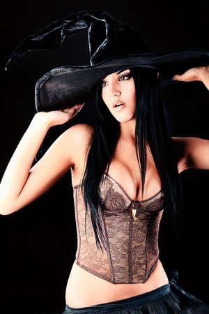 evil girl: Incantevole strega halloween su sfondo nero.