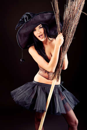 Charming halloween witch with broom over black background. Stock Photo - 11274818