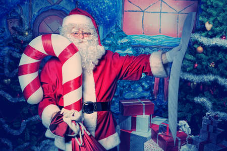 Santa Claus posing with a list of presents over Christmas background. photo