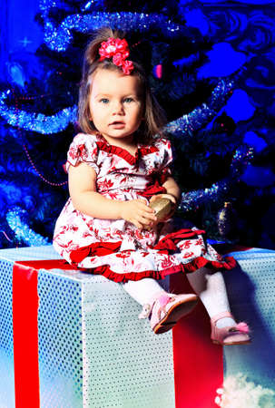 Beautiful child sitting on a big present box against Christmas decoration. Stock Photo - 11340755