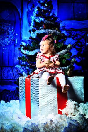 Beautiful child sitting on a big present box against Christmas decoration. Stock Photo - 11337253