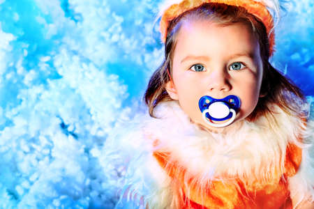 Happy little girl in Christmas costume sitting in snowdrift. Stock Photo - 11340724