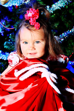 Beautiful child sitting with presents against Christmas decoration. photo