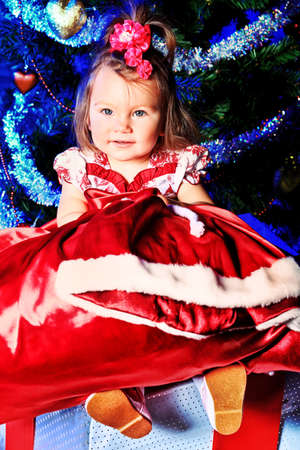 Beautiful child sitting with presents against Christmas decoration. Stock Photo - 11340738