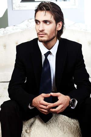 caras emociones: Retrato de un hombre guapo de moda posando en el interior.