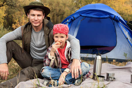 camping equipment: Happy father with his son having a rest outdoor in tent.