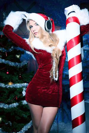 Bella giovane donna in abiti di Santa Claus e le cuffie su sfondo natalizio.
