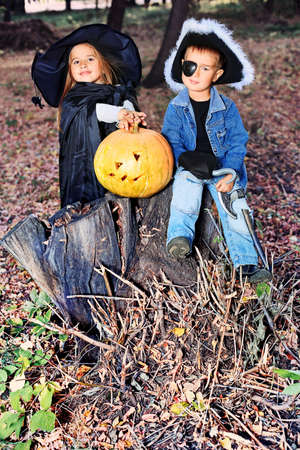 Shot of a children in halloween costumes posing with pumpkin outdoor. photo
