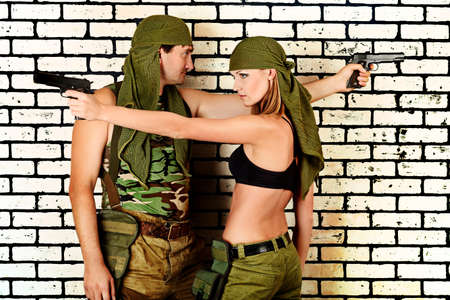 Shot of a military couple posing against brick wall. photo