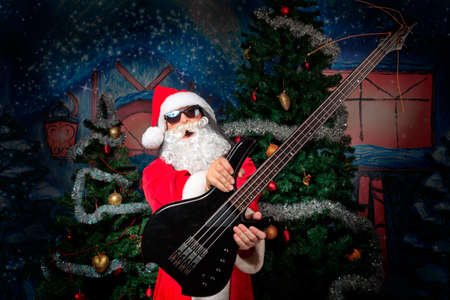 heavy metal music: Portrait of a singing Santa Claus with electric guitar. Christmas. Stock Photo
