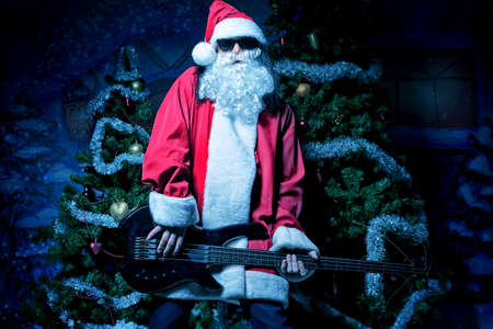 Portrait of a singing Santa Claus with electric guitar. Christmas. Stock Photo