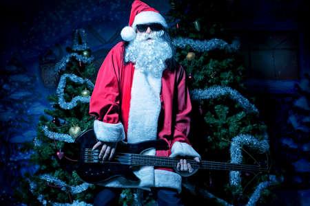 claus: Retrato de un Santa Claus cantando con la guitarra el�ctrica. Navidad. Foto de archivo
