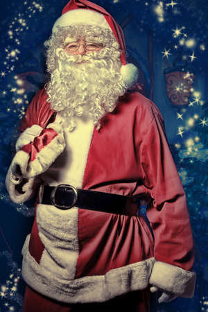 Santa Claus posing with presents over Christmas background. Stock Photo - 11340539