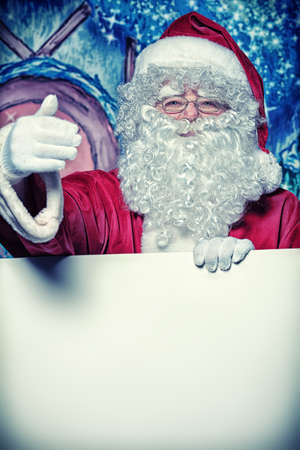 nick: Santa Claus holding white board over Christmas background.