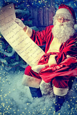 christmas list: Santa Claus posing with a list of presents over Christmas background.