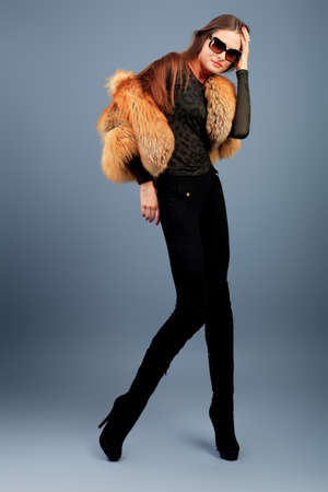 Portrait of a beautiful young woman in a fur over grey background. Stock Photo - 11340413