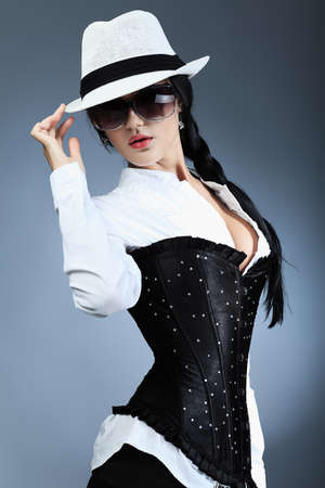 girl in a hat: Fashion photo, a model is posing over grey background