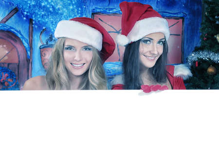 new love: Two sexy young women in Christmas clothes holding white board over Christmas background.
