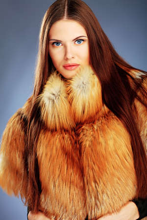Portrait of a beautiful young woman in a fur over grey background. Stock Photo