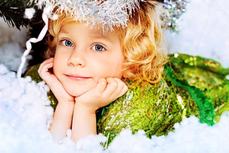 Happy little girl in Christmas dress lying in snow. Stock Photo - 11420088
