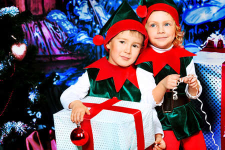 Two cute children in christmas elf costumes posing over christmas background. Stock Photo - 11419236