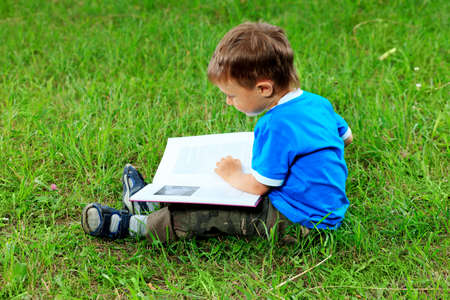 child reading: Shot of a little boy with a book having a rest outdoor.