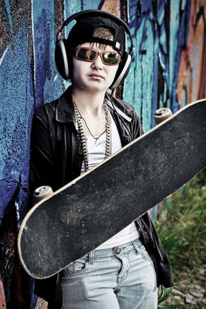 Portrait of a trendy boy teenager with headphones and skateboard outdoors. photo