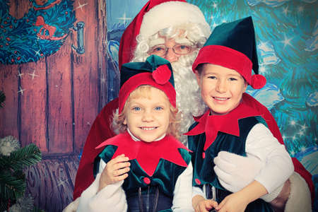 Santa Claus sitting with two little cute elves over Christmas background.