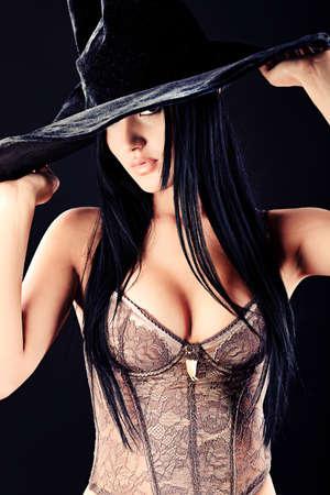 bruja sexy: Casa de la bruja de Halloween sobre fondo negro.