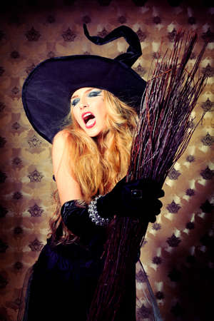 sexy witch: Charming halloween witch with broom over vintage background.