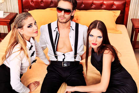 sexy lovers: Portrait of a handsome fashionable man with two charming women posing in the interior. Stock Photo