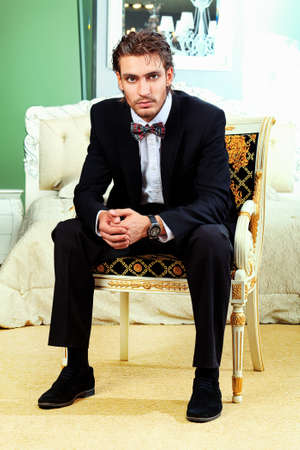 man in tuxedo: Portrait of a handsome fashionable man posing in the interior. Stock Photo