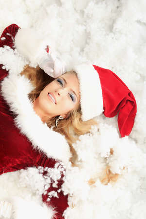 Beautiful young woman in Santa Claus clothes lying in snow. photo
