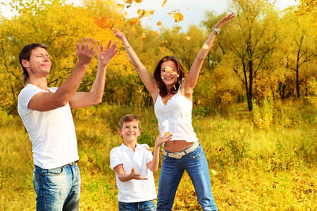 weekends: Happy family having a rest outdoor in the autumn park. Stock Photo