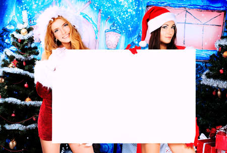 Two sexy young women in Christmas clothes holding white board over Christmas background.