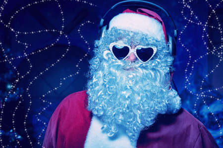 Santa Claus is listening to music in headphones. Christmas. Stock Photo