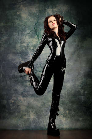 latex girl: Fashion shot of a woman in black glossy overall and platform boots.