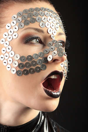 latex girl: Conceptual shot of a woman in black glossy overall and metal buttons on her face.