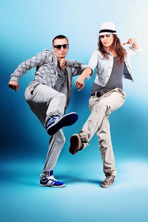 woman dancing: A couple of young man and woman dancing hip-hop at studio. Stock Photo