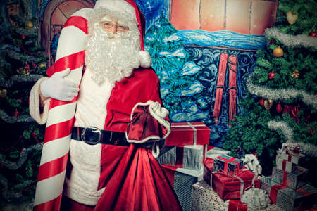 Santa Claus posing with presents over Christmas background. Stock Photo - 11639218