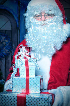 Santa Claus posing with presents over Christmas background. Stock Photo - 11639221