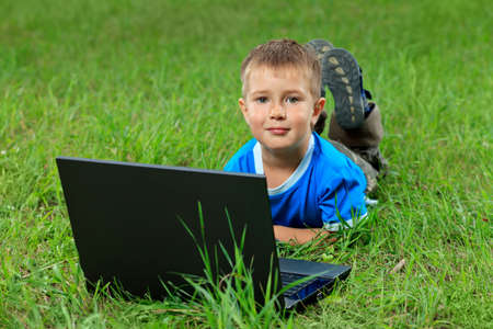 Portrait of a little boy lying with his laptop on a grass at a park. photo