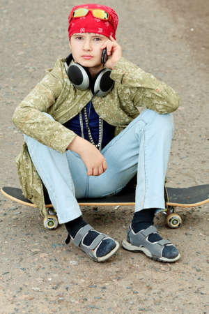Portrait of a trendy boy teenager with skateboard outdoors. photo